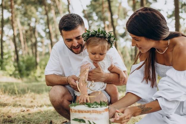 Familie mit kleiner tochter, die ersten geburtstag feiert