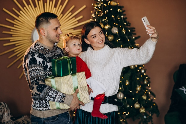 Familie mit kleiner tochter durch den weihnachtsbaum, der geschenkbox auspackt