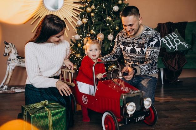 Familie mit kleiner tochter mit weihnachtsgeschenk durch weihnachtsbaum