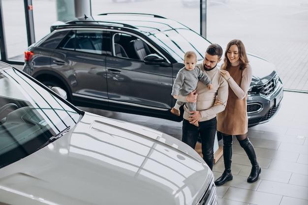 Familie mit kleinkindmädchen, das ein auto in einem autohaus wählt