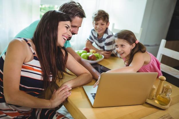 Familie mit laptop am esstisch