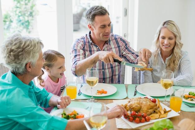 Familie mit mehreren generationen beim essen am esstisch
