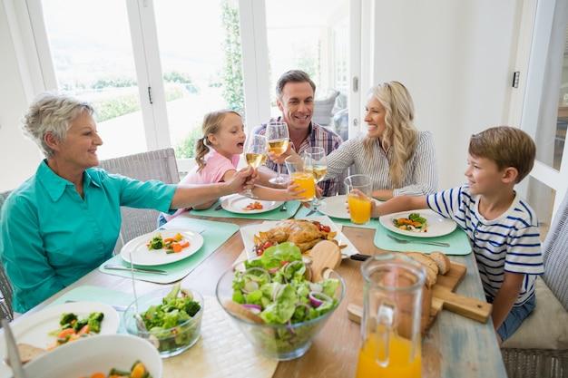 Familie mit mehreren generationen, die ein glas wein und saft auf dem esstisch röstet