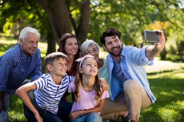 Familie mit mehreren generationen, die ein selfie auf dem mobiltelefon nimmt
