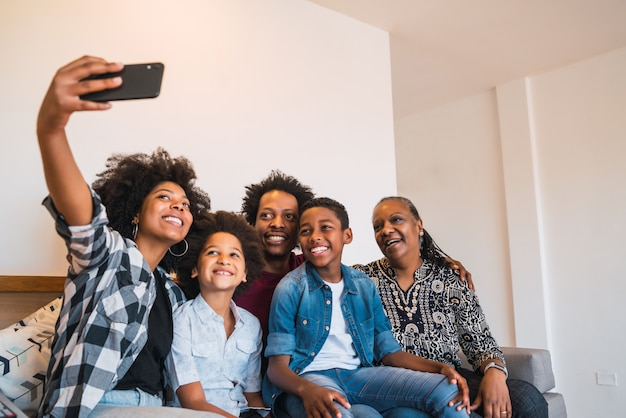 Familie mit mehreren generationen, die selfie mit telefon zu hause nimmt.