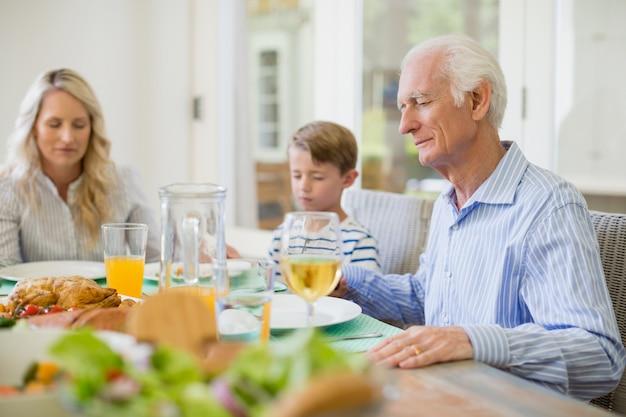 Familie mit mehreren generationen, die vor dem essen betet