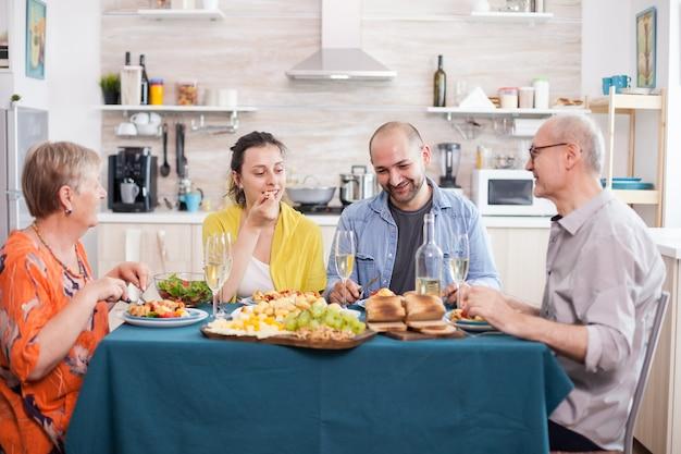 Familie mit mehreren generationen lächelt während des mittagessens, genießt leckere kartoffeln und erzählt witze. leckere bratkartoffeln auf dem esstisch.