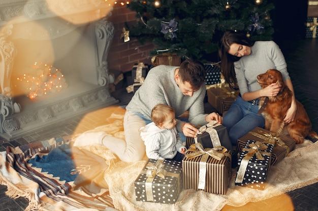 Familie mit niedlichem hund zu hause nahe weihnachtsbaum