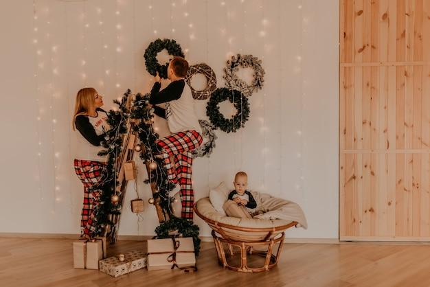 Familie mit schwangerer frau auf trittleiter schmückt das haus für das kleine neujahrsbaby, das auf einem stuhl sitzt und spielt. weihnachtsmorgen. silvester interieur. valentinstag feier
