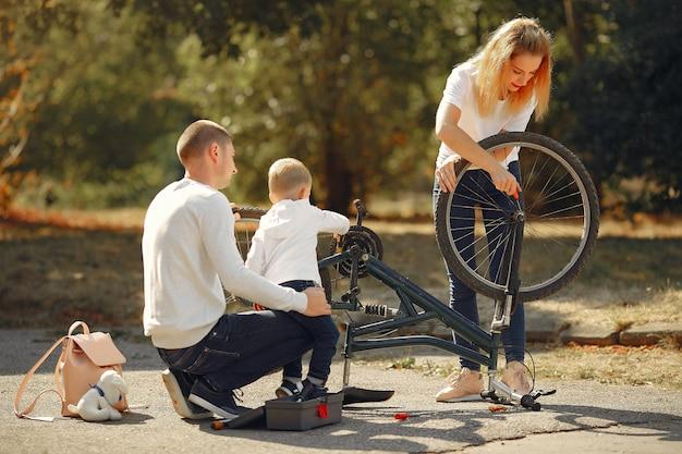 Familie mit sohn reparieren das fahrrad in einem park