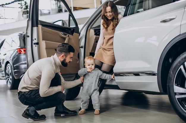 Familie mit süßer tochter, die ein auto in einem autohaus wählt