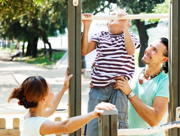 Familie mit teenager-sohn-training auf pull-up-bar