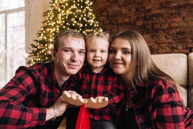 Familie mit tochter feiern weihnachten zu hause in der nähe des baumes und tauschen geschenke aus
