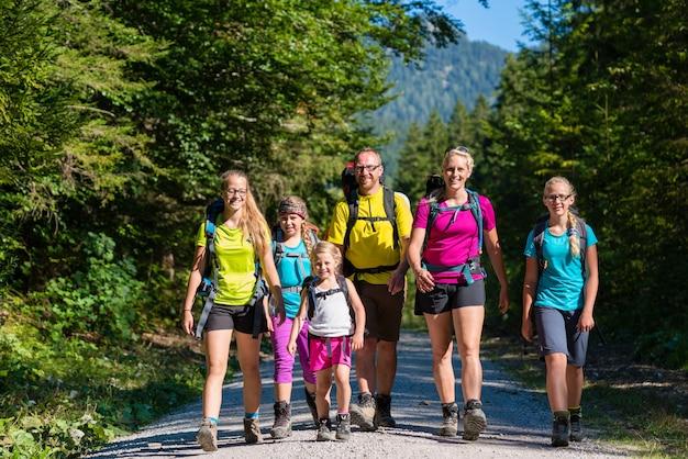 Familie mit vier kindern, die in den bergen wandern
