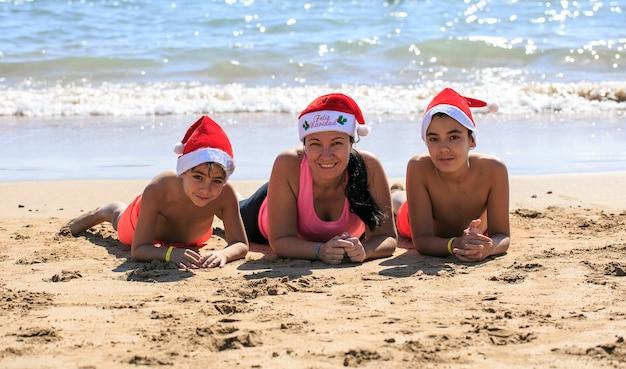 Familie mit weihnachtsmütze am strand