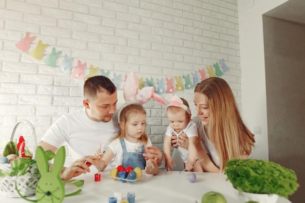 Familie mit zwei kindern in einer küche, die ostern vorbereitet