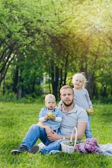 Familie mit zwei kindern ruht im sommergarten
