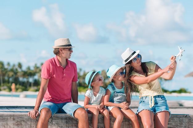 Familie mit zwei kindern spielen am tropischen strand laufen