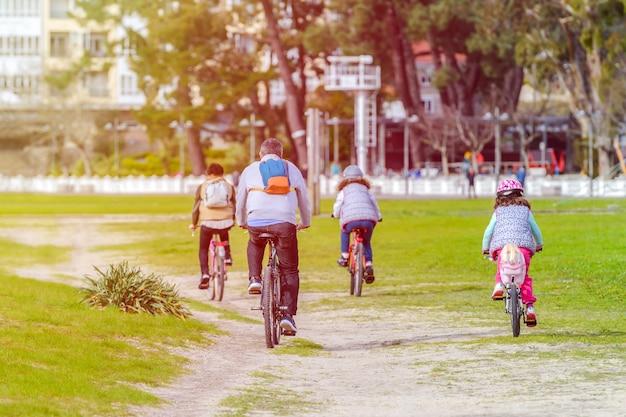 Familie mit zwei töchtern, die fahrrad in einem stadtpark fahren, einen sicheren abstand halten, rückansicht, mit warmen farben tönend