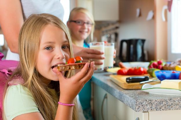 Familie, mutter, die frühstück für die schule macht