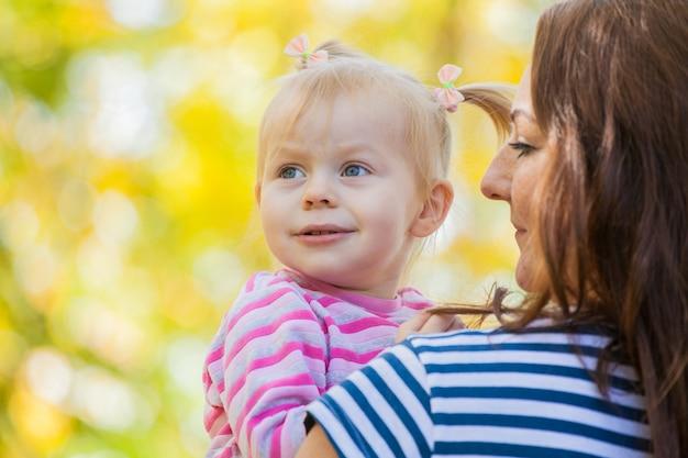 Familie mutter und tochter auf einem spaziergang im park im herbst. in mamas sicheren händen