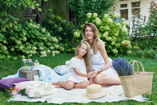 Familie mutter und tochter im garten im sommer auf einem picknick ausruhen
