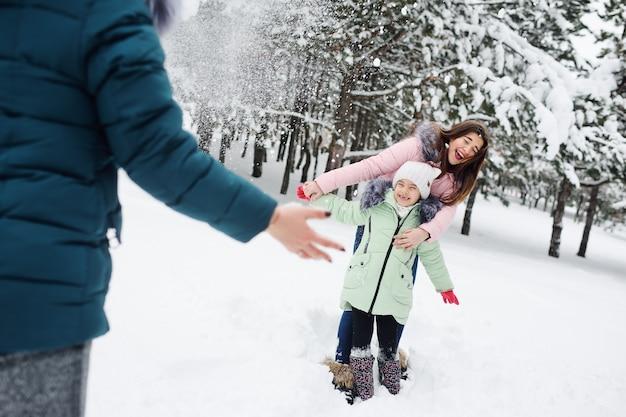 Familie, mutter und zwei töchter haben spaß und spielen vor dem hintergrund schneebedeckter bäume und wälder. winterspaß