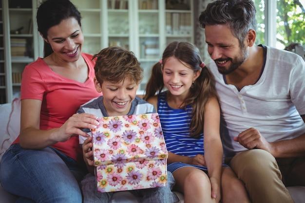Familie öffnet das überraschungsgeschenk im wohnzimmer