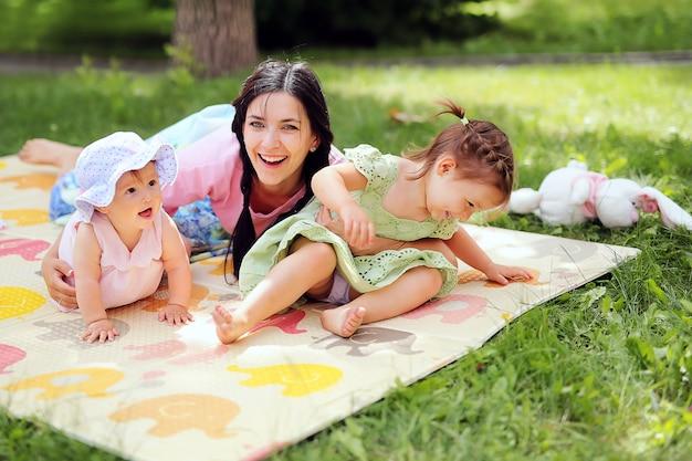 Familie. porträt der schönen netten mutter mit ihren netten töchtern, die spaß zusammen im sommerpark haben. junge frau, die ihre kleinkinder hält