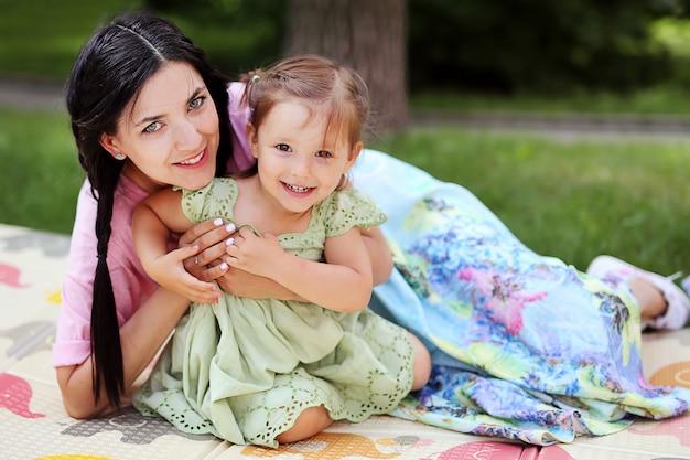 Familie. porträt der schönen netten mutter mit ihrer netten tochter, die spaß zusammen im sommerpark hat. frau mit kleinem mädchen auf dem gras