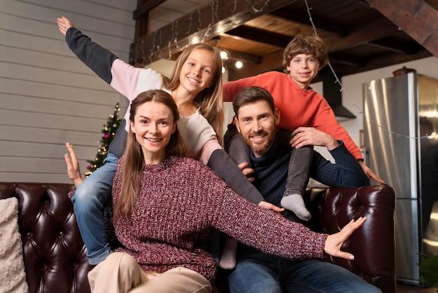 Familie posiert zusammen neben einem weihnachtsbaum