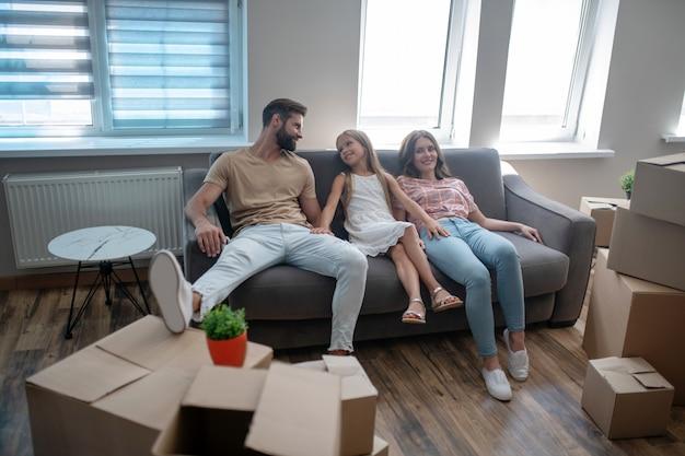 Familie ruht auf dem sofa nach dem umzug in ein neues haus