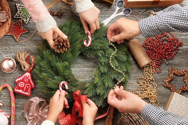 Familie schmückt weihnachtskranz auf holzoberfläche