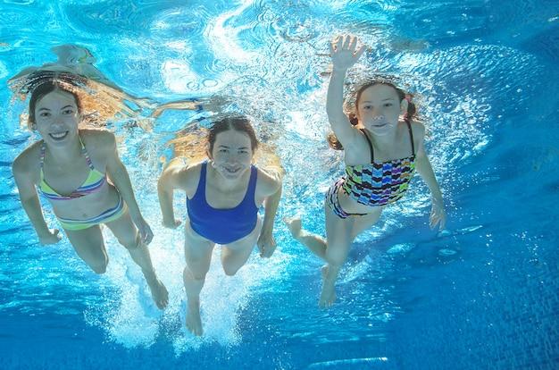 Familie schwimmt im pool unter wasser, glückliche aktive mutter und kinder haben spaß unter wasser, fitness und sport mit kindern in den sommerferien im resort