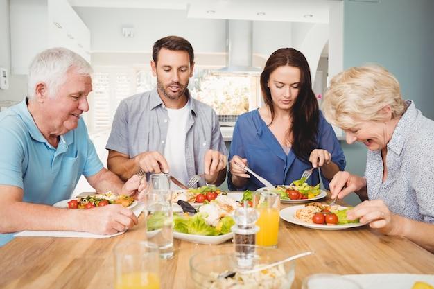Familie sitzt am esstisch mit essen