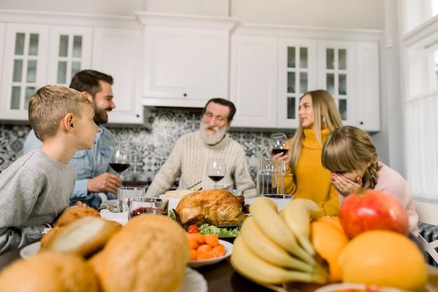 Familie sitzt am tisch und feiert urlaub. großvater, eltern und kinder. traditionelles abendessen. konzentriere dich auf den truthahn