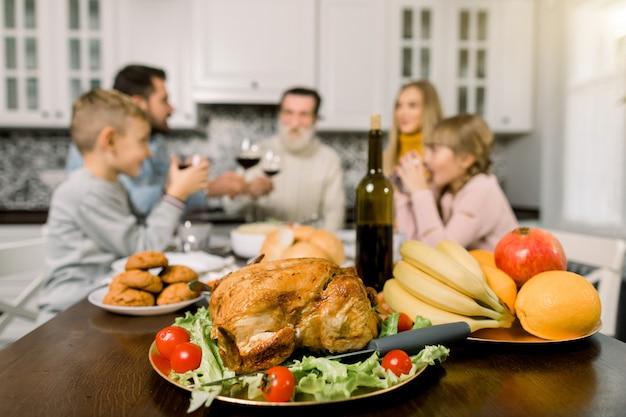Familie sitzt am tisch und feiert urlaub. großvater, mutter, vater und kinder. traditioneller truthahn, obst und wein auf dem tisch. konzentrieren sie sich auf die türkei