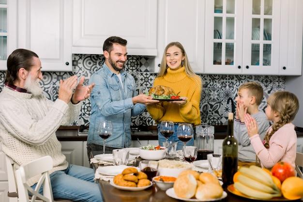 Familie sitzt am tisch und feiert urlaub. traditionelles abendessen. drei generationen familie. junge eltern halten truthahnbraten und lächeln