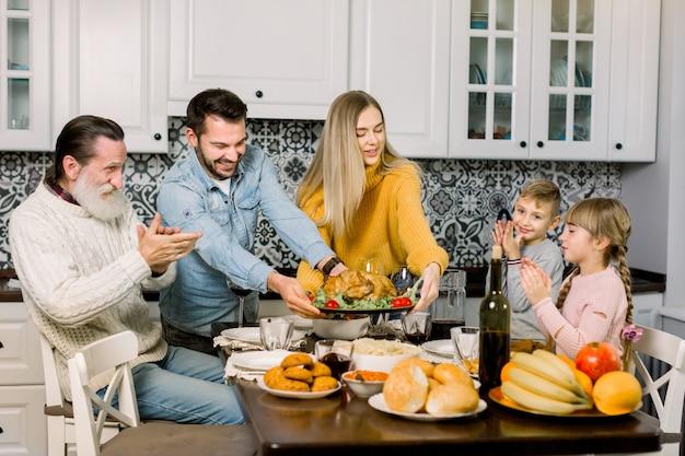 Familie sitzt am tisch und feiert urlaub