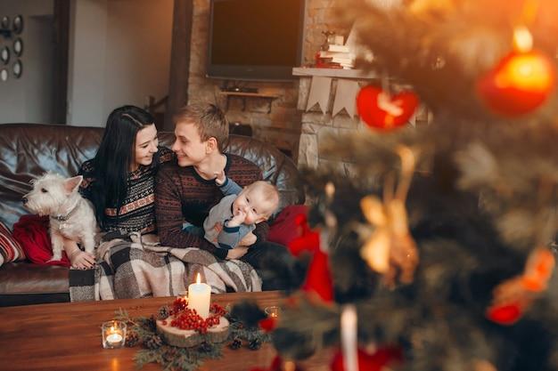 Familie sitzt auf der couch mit weihnachtsbaum unscharf vor