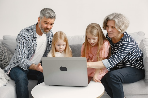 Familie sitzt auf der couch. reifer mann und frau spielen mit enkelinnen im laptop. technologie-konzept.