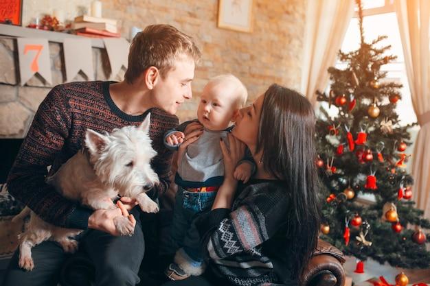 Familie sitzt auf einem sofa mit hund zu weihnachten