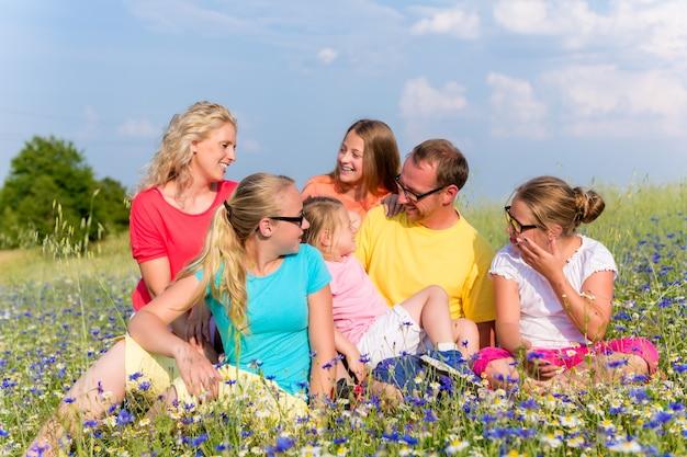 Familie sitzt auf wiese in blumen, mama, papa und den kindern