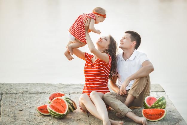 Familie sitzt in der nähe des wassers auf der brücke