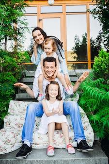 Familie sitzt in der reihe auf schritten vor dem haus
