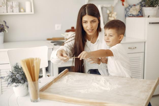 Familie sitzt in einer küche und kocht den teig für kekse