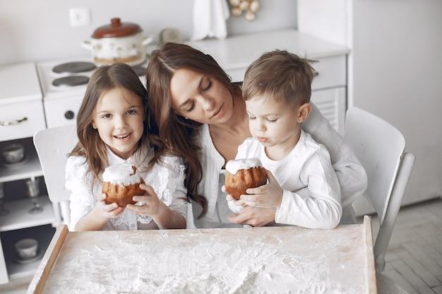 Familie sitzt in einer küche und kocht den teig für kuchen