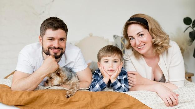Familie sitzt mit ihrem hund auf dem bett