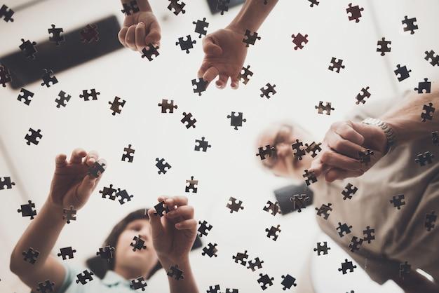 Familie spielt das puzzlespiel, das nach stücken auf tabelle sucht