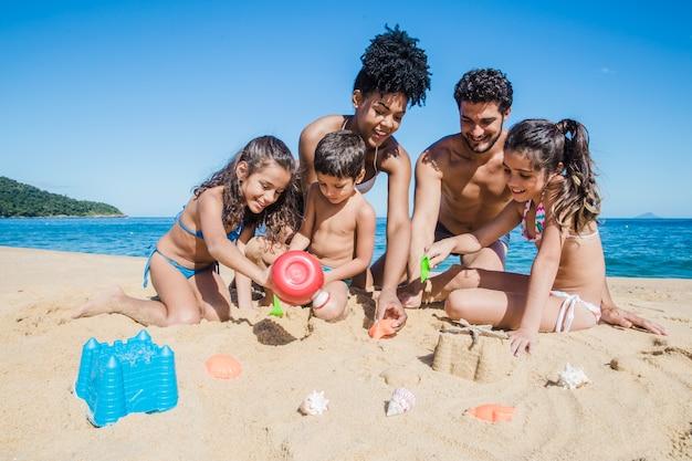 Familie spielt mit dem sand